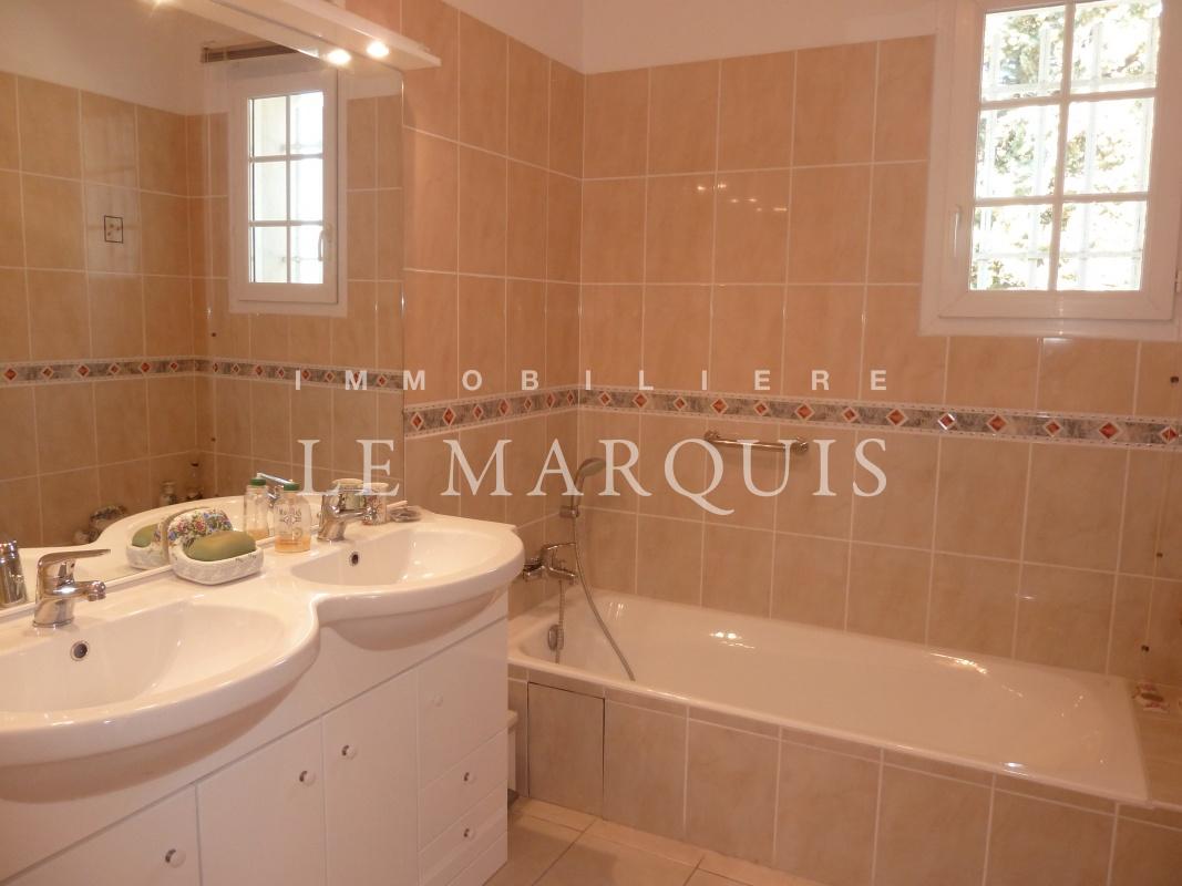 La fenêtre donne de la luminosité à la salle de bain carrelée